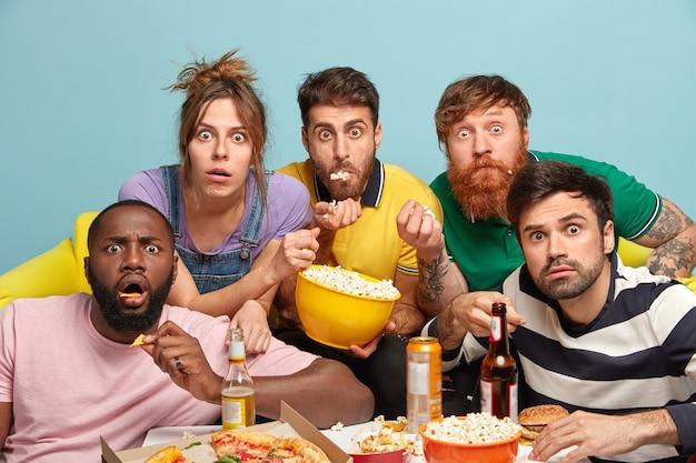 I migliori amici stupiti guardano film dell'orrore a casa, fissano con gli occhi fuoriusciti, mangiano popcorn, bevono bevande alcoliche fredde, goditi la tv in streaming, non credere a qualcosa, isolato su un muro blu