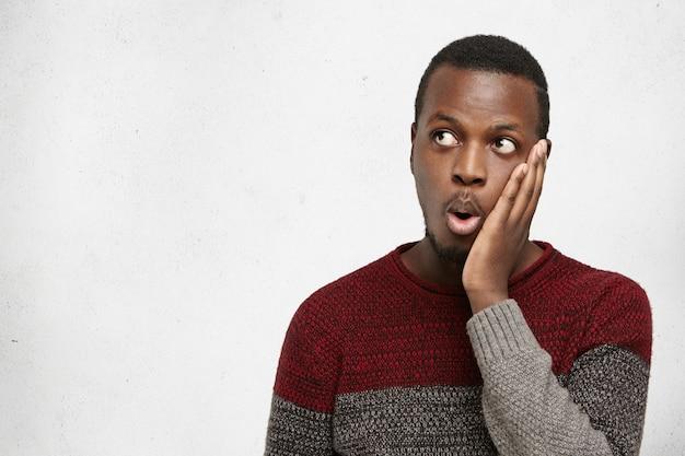 Fronte commovente stupito dell'uomo di colore, esaminando copyspace sulla parete grigia in bianco, colpito con qualcosa. emotivo divertente giovane maschio afroamericano che esprime shock, dicendo: questo è incredibile!