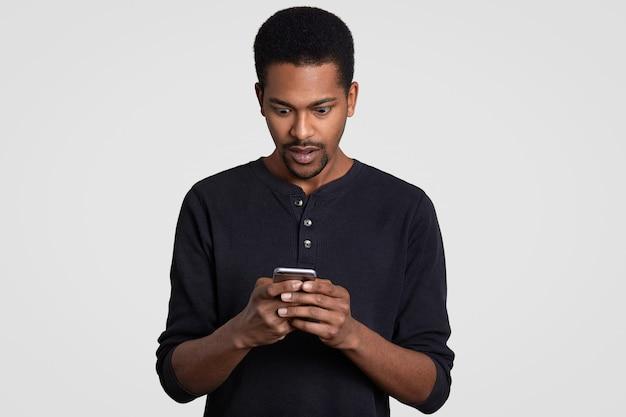 巻き毛のびっくりした黒人男性、携帯電話を持っている、テキストメッセージを受信する、驚いた、驚いた、カジュアルな服を着ている