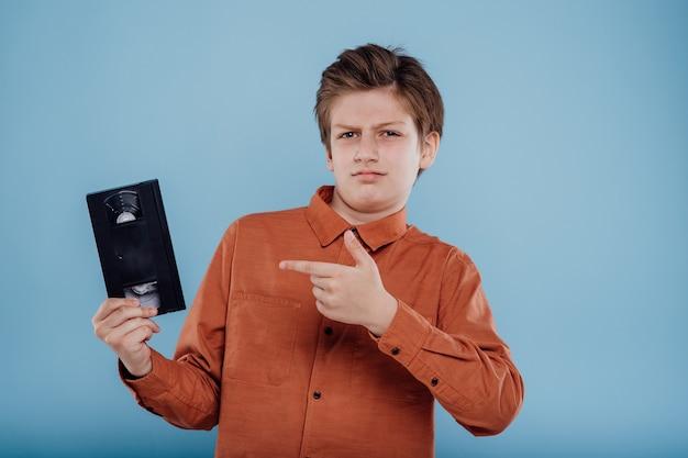파란색 배경 오래된 가제트에 격리된 비디오 테이프로 놀란 소년