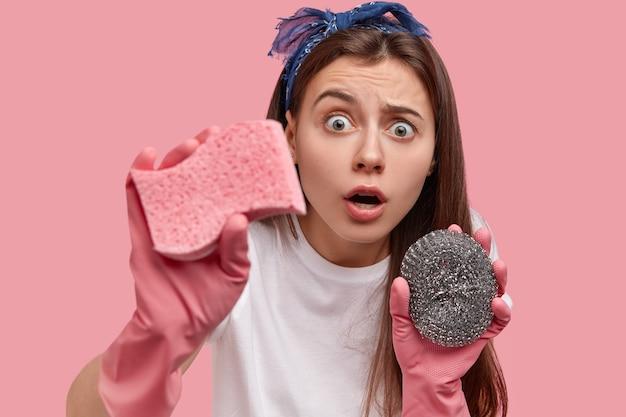 Удивленная брюнетка выглядит с испуганным выражением лица, с отвисшей челюстью, использует губки для уборки квартиры или гостиничного номера, боится большого количества грязи