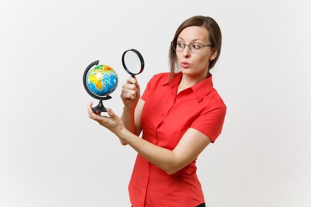 흰색 배경에 격리된 세계에서 돋보기를 들고 보고 있는 빨간 셔츠를 입은 비즈니스 교사 여성을 놀라게 했습니다. 고등학교 대학 개념에서 교육 교육입니다. 공간을 복사합니다.