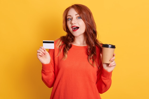 Astonished buyer finding offer online, holding take away coffee and credit card, has surprised facial expression, lady with red lips and wavy hair