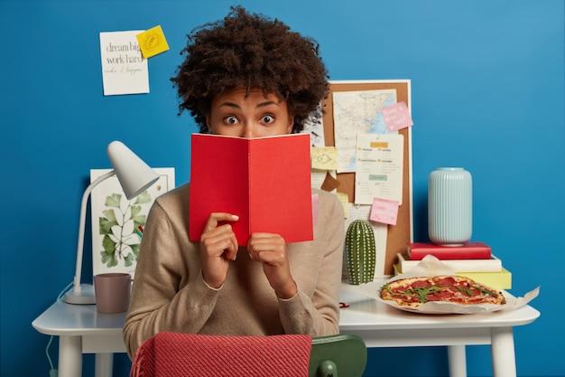 Stupito studente universitario copre il viso con un diario rosso, scioccato per dimenticare un compito importante da preparare