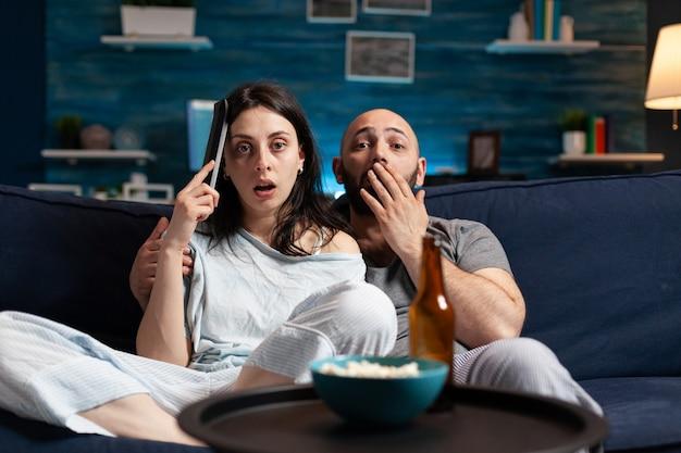 Удивленная пара смотрит фильм ночью и ест попкорн, попивая пиво