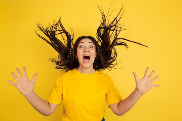 Astonished, crazy. caucasian woman's portrait isolated on yellow wall.