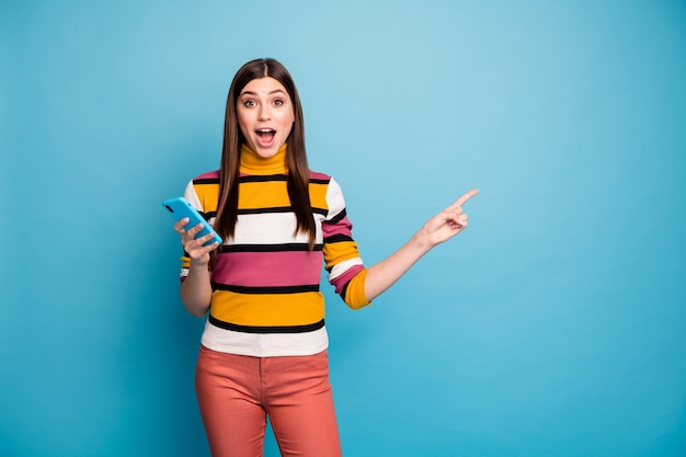 Astonished crazy girl point index finger copyspace use smart phone indicate incredible ads promotion impressed scream wow omg wear red pants trousers jumper isolated blue color wall