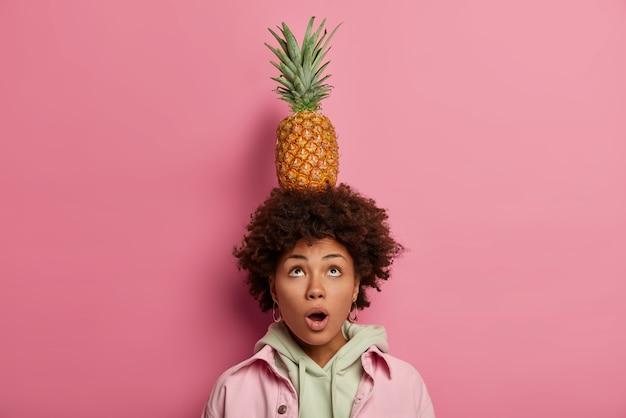 驚いた巻き毛のアフリカ系アメリカ人の女性が上を見て、口を開けたまま、パイナップルを頭に乗せ、どうすればいいのか疑問に思い、パーカーとジャケットを着て、ピンクのパステルカラーの壁にポーズをとる。