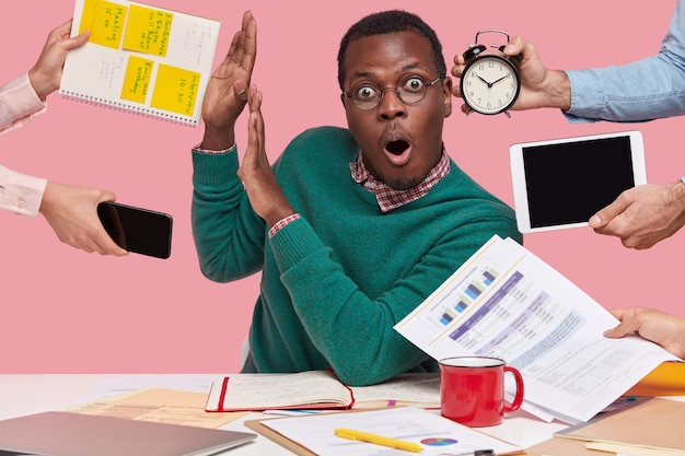 Удивленный смуглый молодой человек с шокирующим выражением лица делает стоп-жест, просит не возиться с работой, записывает информацию в блокнот