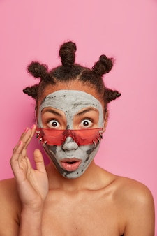 La donna stupita e emotiva fissa con gli occhi ben aperti, indossa occhiali da sole alla moda, applica una maschera per il viso di bellezza, posa a torso nudo al coperto contro un muro roseo. trattamenti viso, cura della pelle cocept