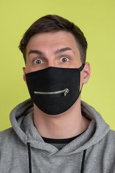 びっくりした目。黄色のスタジオの壁に分離された白人男性の肖像画。黒のフェイスマスクの男性モデル。