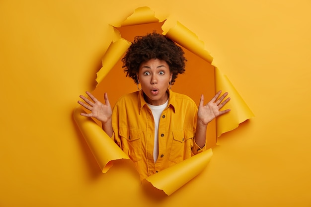 Astonished fascinated ethnic girl raises palms, cannot believe in horrible situation happened with her, dressed in stylish clothing, poses at ripped paper hole, gets stunning chance.
