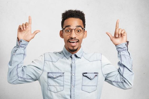 Astonished fashionable guy with appealing appearance raises fingers up, indicates upwards