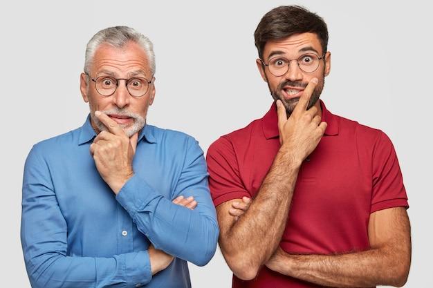 Удивленный отец и молодой взрослый сын позируют у белой стены