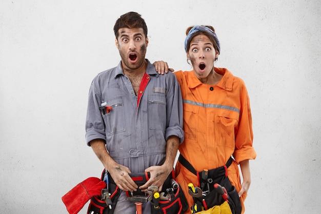 口を大きく開けて驚いた女性と男性の技術者