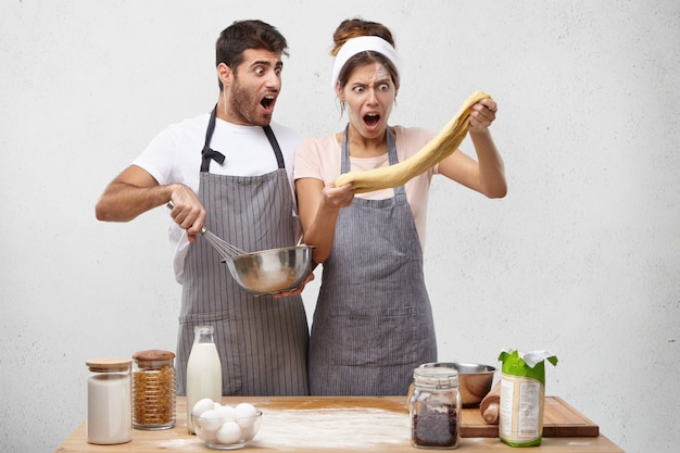 Astonished female chef stretches dough, looks with great surprisment, realizes drawbacks of preparation