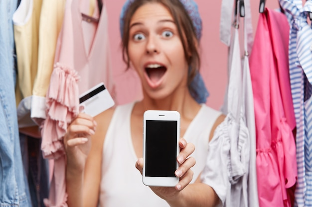 Astonished female model looking with bugged eyes and widely opened mouth while holding credit card in one hand and smart phone with blank screen in other, standing in her cloakroom