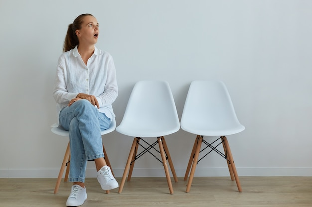 Удивленная женщина в повседневной одежде сидит на стуле и смотрит в сторону с широко открытым ртом, видит что-то шокированное, удивленное производит впечатление.