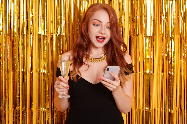 Astonished female with red lips and widely opened mouth, looking with shocked facial expression at her device, girl wearing black dress, posing isolated over wall decorated with golden tinsel.