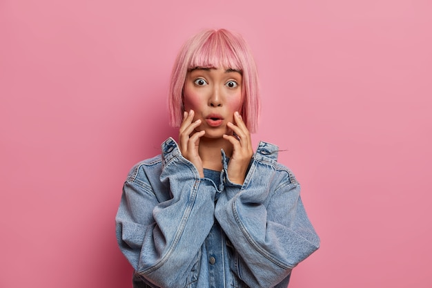 Astonished frightened alarmed asian woman grabs face and stares, has bob pink hair, scared by something, gasps from fear, witnesses terrible accident, wears oversized denim jacket.