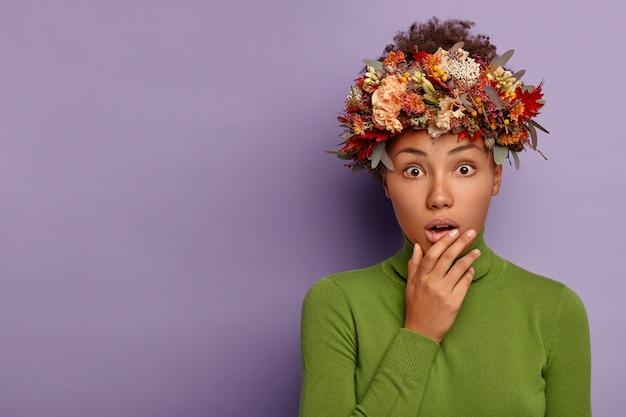 驚いた怯えた民族の女性は恐怖からあえぎ、あごに触れ、魅了されたニュースに反応し、紫色の背景の上に隔離された緑の服を着た秋の植物で作られた秋の花輪を着ています。