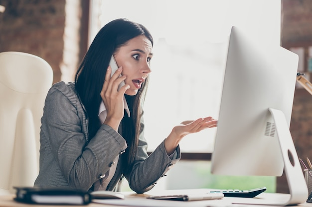 Astonished frustrated girl collar call smartphone boss impressed crisis way-out plan development mistake report work remote pc computer sit table wear blazer jacket in workplace workstation