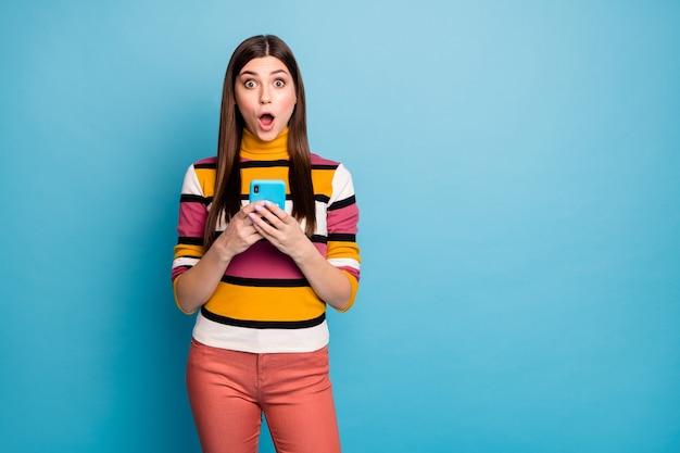 驚いたファンキーな女の子中毒のソーシャルネットワークユーザーはスマートフォンを使用するブロガーのコメントを読む購読感動悲鳴信じられないほどの予期しない服スタイリッシュな服孤立した青い色の壁