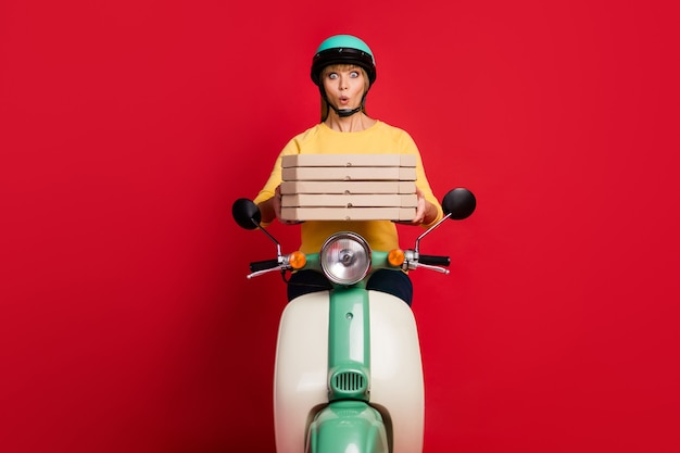 Astonished funky girl cafeteria worker ride bike hold stack of pizza box