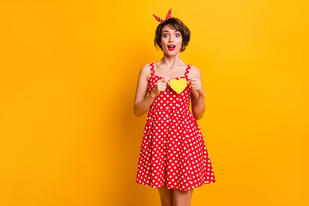 Удивленная забавная девушка празднует дату 14 февраля, держа желтую маленькую бумажную карточку в виде сердца, она получает страстный парень, одетый в винтажном стиле, красная яркая юбка, изолированный блеск, цвет стены