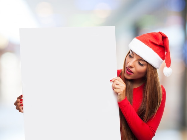 Astonished girl holding an empty poster with blurred background