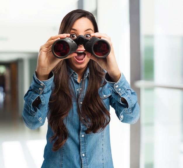 Astonished girl with binoculars