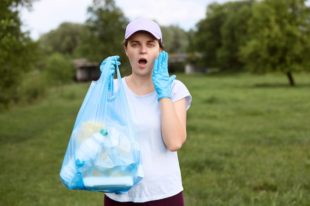 Astonished girl with widely opened mouth stands with garbage bag in hand, keeping palm on her cheek