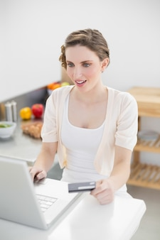 Astonished gorgeous woman using her notebook for home shopping in her kitchen