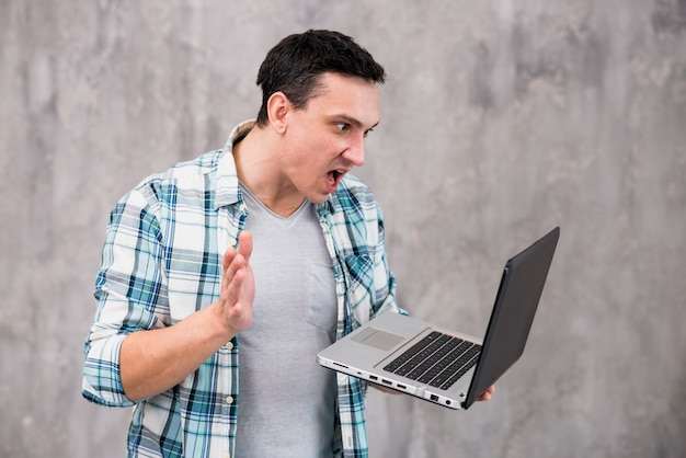 Astonished guy with laptop and opened mouth