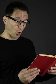 Astonished handsome dark hair casual dressed 40s man in glasses reads book