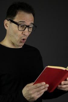 驚いたハンサムな黒髪のカジュアルなメガネをかけた40代男性が本を読む