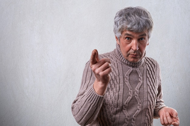 An astonished handsome elderly man with gray hair dressed in sweater standing near white wall pointing with finger wanting
