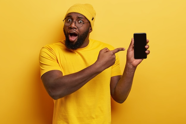 Удивленный красивый парень в очках позирует со своим телефоном
