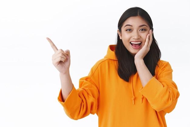La ragazza asiatica felice e stupita ha trovato il miglior affare fantastico che te lo mostra, puntando il dito nell'angolo in alto a sinistra della pubblicità e sorridendo stupito, toccando la guancia arrossata e sorpresa, muro bianco