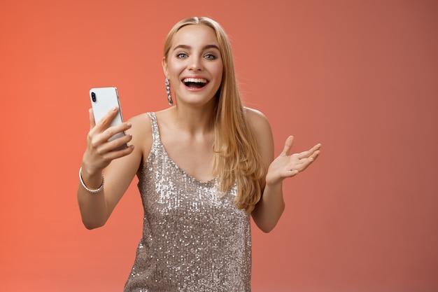 Удивленная счастливая очаровательная белокурая девушка в серебристом блестящем стильном платье со смартфоном, восхищенная потрясающим результатом, приложение для редактирования фотографий, улыбающаяся, удивленная, удивленная, стоит на красном фоне.