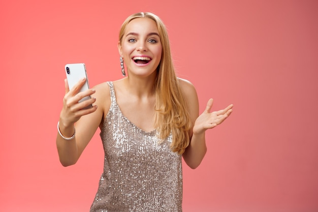 Astonished happy charming blond girl in silver glittering stylish dress holding smartphone amazed liking awesome result edit photo app smiling wondered amused, standing red background.
