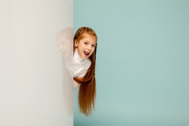 Astonished. happy kid, girl isolated on blue studio background. looks happy, cheerful. copyspace for ad. childhood, education, emotions, facial expression concept. peeking out from behind the wall.