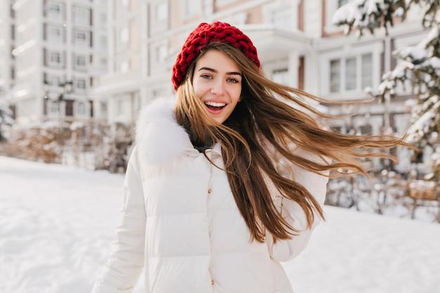 Donna felice stupita in cappello rosso divertendosi nella mattina congelata sulla strada piena di neve. esprimere positività, vere emozioni allegre