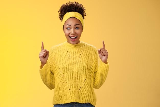 Удивленная впечатленная афро-американская девушка с отвисшей челюстью удивленно расширила глаза, удивленно подняв указательные пальцы, реагируя на невероятно удивительный торговый центр со скидкой, стоящий на желтом фоне.