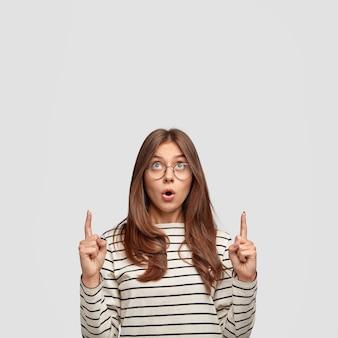 놀랍게도 갈색 머리를 가진 유럽 여성은 턱을 떨어 뜨리고 위층을 가리키며 광고 콘텐츠를위한 여유 공간을 보여주고 흰 벽에 서 있습니다. 광고