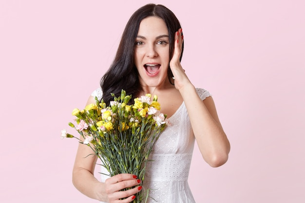 Astonished impressed young lady stands isolated over pink, opens mouth widely in surprise, holding bouquet of spring flowers