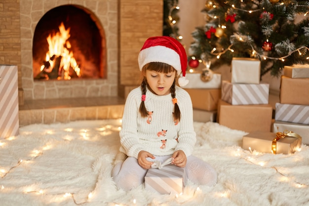 Astonished little girl on christmas eve at fireplace. kid opens xmas present. child in decorated living room with traditional fire place. cozy winter evening at home. surprised female kid on floor.