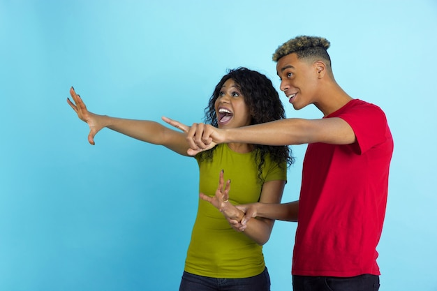 Astonished look at side like sport fans. young emotional african-american man and woman in colorful clothes on blue wall.