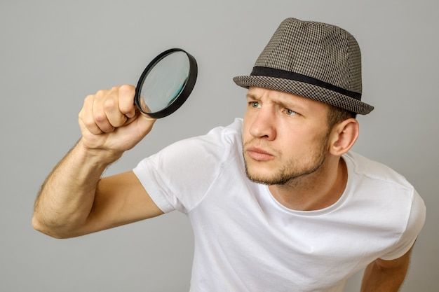 Astonished man looking through a magnifying glass