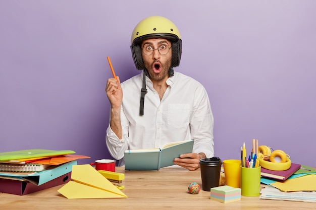 Astonished man student writes some ideas in notebook, raises arm with pen, wears helmet on head, spectacles, drinks takeaway coffee, surrounded with necessary stationery on workplace, makes notes